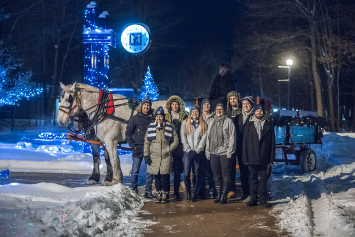 Students gather next to a horse-drawn carriage at Northwood University